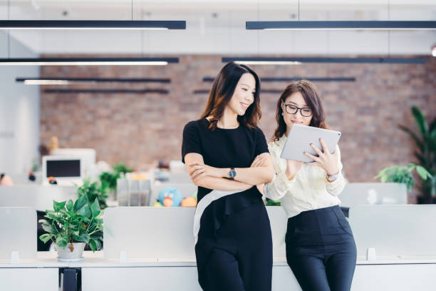Asian business people working on digital tabler together in bright office stock photo