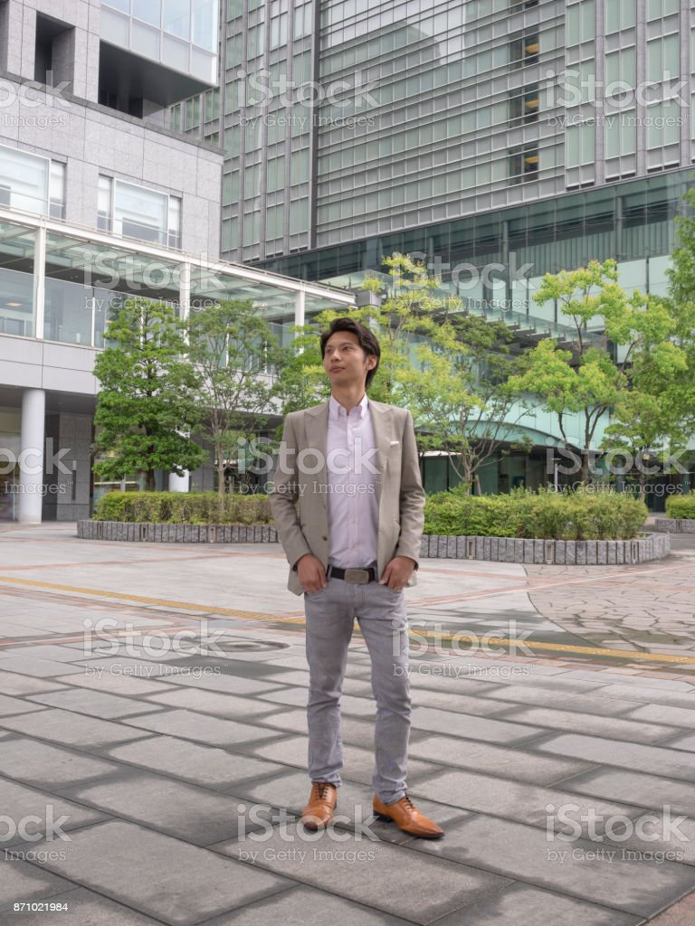 Asian business person standing on the business park. stock photo