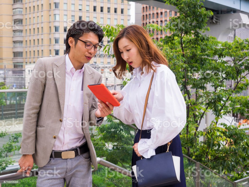 Asian business persons watching tablet on the street. stock photo