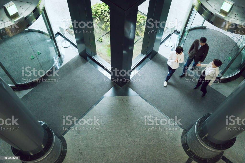 アジア ビジネス チーム メンバー、事務所の入口で会う ストックフォト