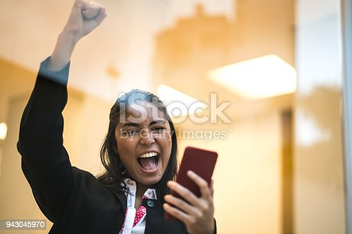 istock Asian Business Woman Celebrating with Mobile Phone 943045970
