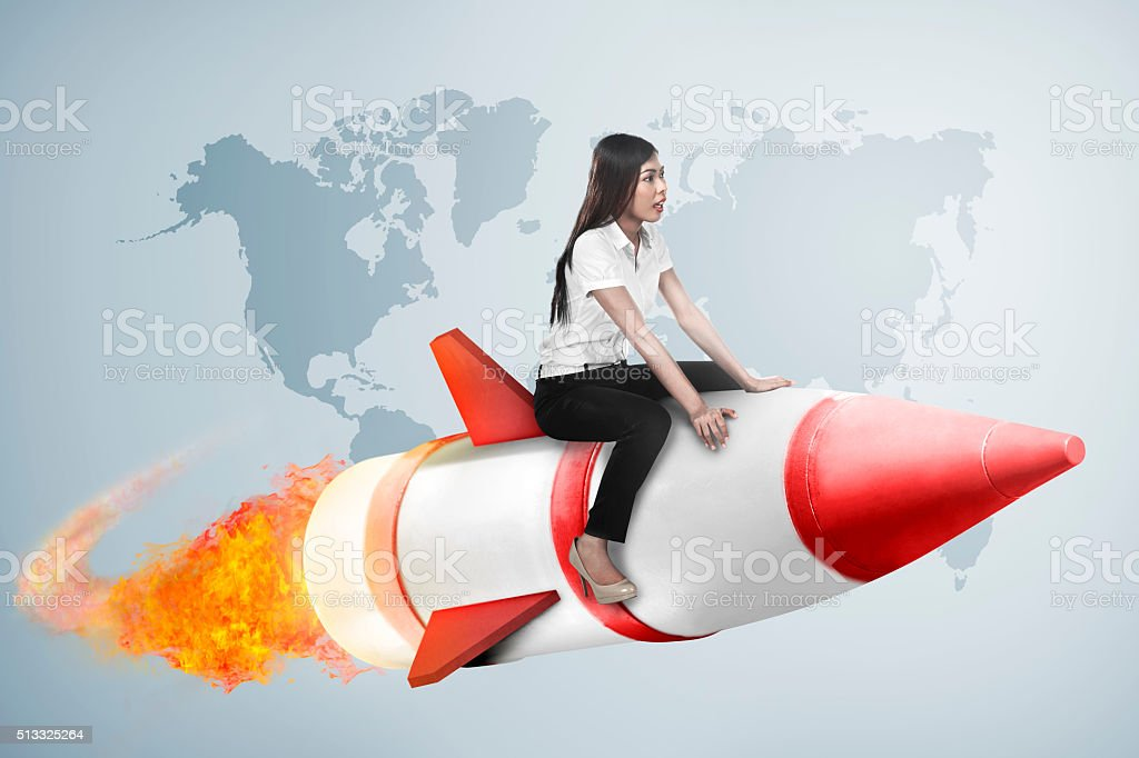 asian business woman flying ride rocket stock photo