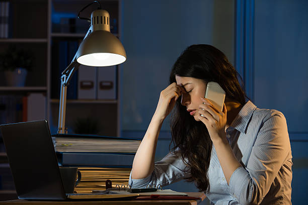 asian business woman headache on smartphone working overtime stock photo