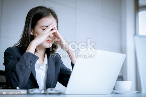 istock Asian business woman headache stressed because of work mistake problems about profit losses to be risk for fired from her job 1016737662