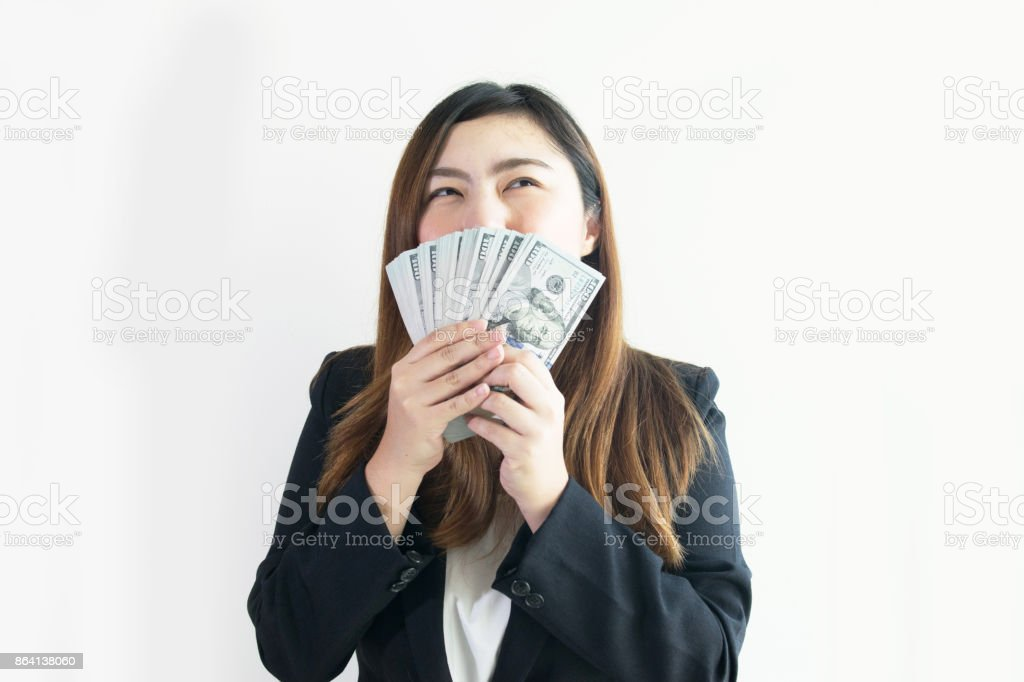 Asian business woman is enjoy with big money US Dollar notes on white background isolated. royalty-free stock photo