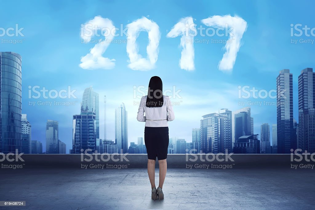 Asian business woman looking cloud shaped number 2017 stock photo