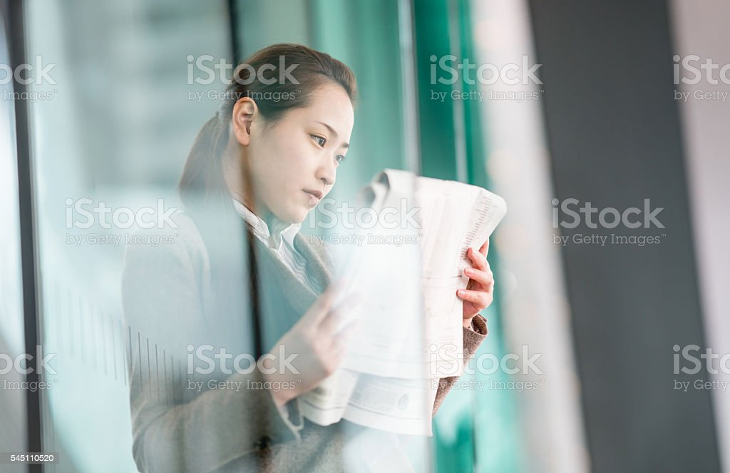 Asian business woman reading the news stock photo