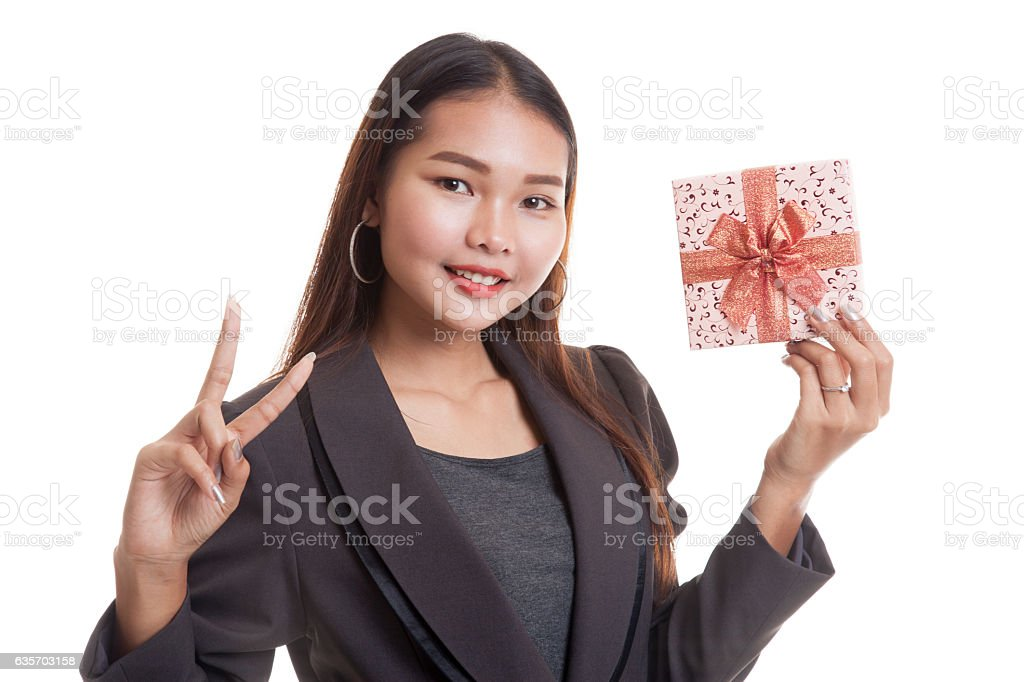 Asian business woman show victory sign with a gift box. royalty-free stock photo