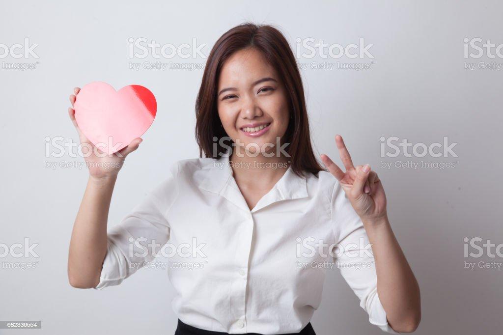 Asiatiska affärskvinna Visa seger tecken med rött hjärta. royaltyfri bildbanksbilder