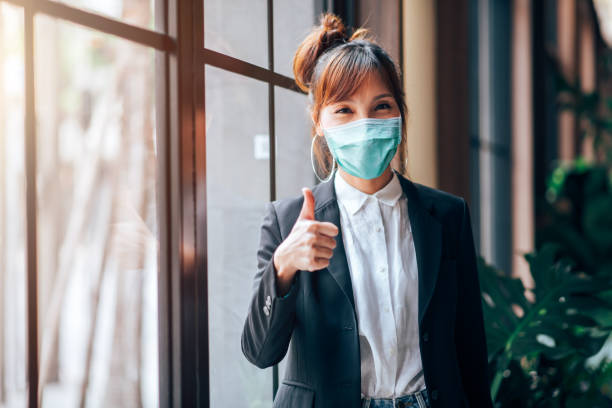 asiatische geschäftsfrau stehen und zeigen daumen nach oben in arbeitsbüro. sie trägt virus schutzmaske in der prävention für coronavirus oder covid-19 ausbruch situation - gesundheitswesen und business-konzept - gestikulieren stock-fotos und bilder