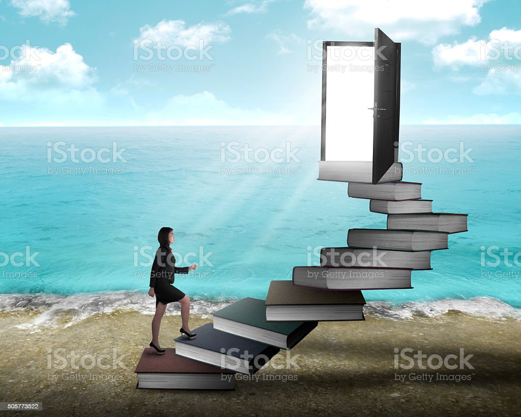 Asian business woman stepping up stair made from book stock photo