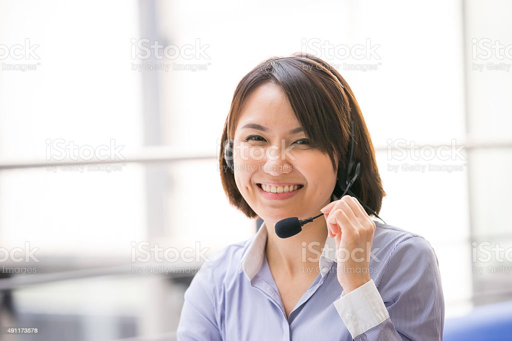Asian Business woman talking using her headset in the office stock photo