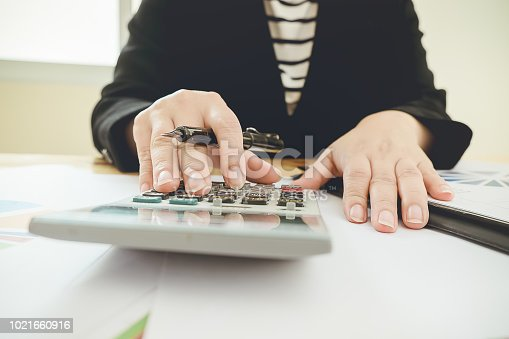 istock Asian Business woman using a calculator to calculate the numbers 1021660916