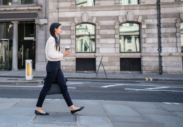 Asian business woman walking on the street drinking a cup of coffee stock photo
