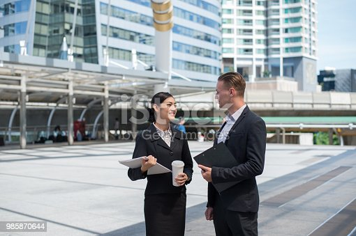 Asian business woman wear suit holding document and talk about business future with Caucasian businessman at the place outside building in the city