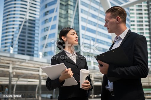 Asian business woman wear suit holding document file and plastic mug on hand talk about business future with  Caucasian businessman in the city.