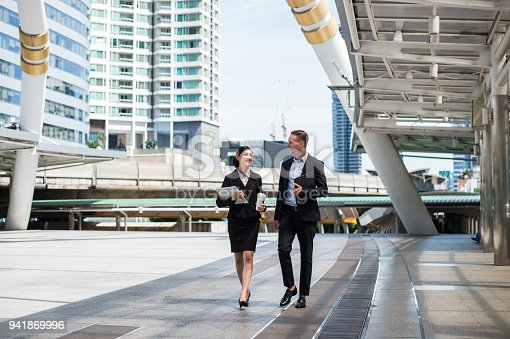 Asian business woman wear suit holding document file and plastic mug on hand walking together with  Caucasian businessman in the city and talk about business future.