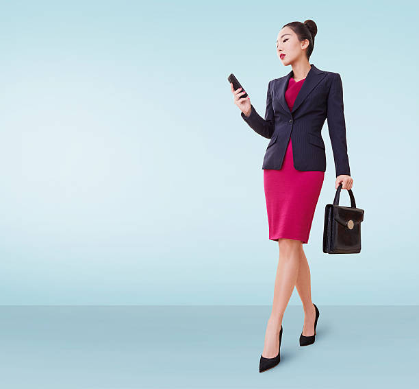 asian business woman with bag and cellphone isolated copyspace. - damen rock pink stock-fotos und bilder