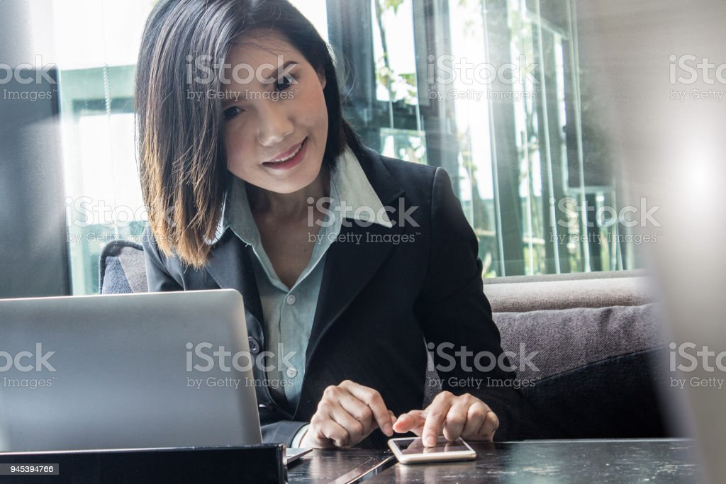 Asian business woman with laptop managing and planning as company CEO in ASEAN region. stock photo