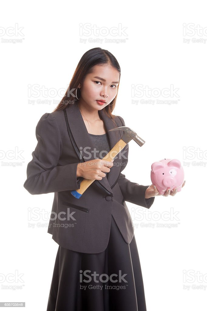 Asian business woman with pig coin bank and hammer. royalty-free stock photo