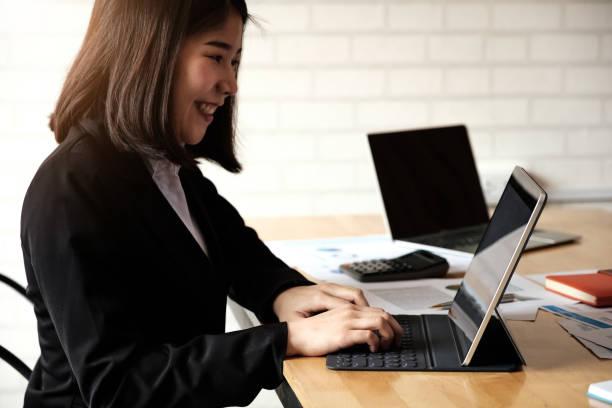Asiatische Geschäftsfrau wacht für finanzielle, kostenpflichtige, Steuern mit Laptop-Computer und Taschenrechner – Foto