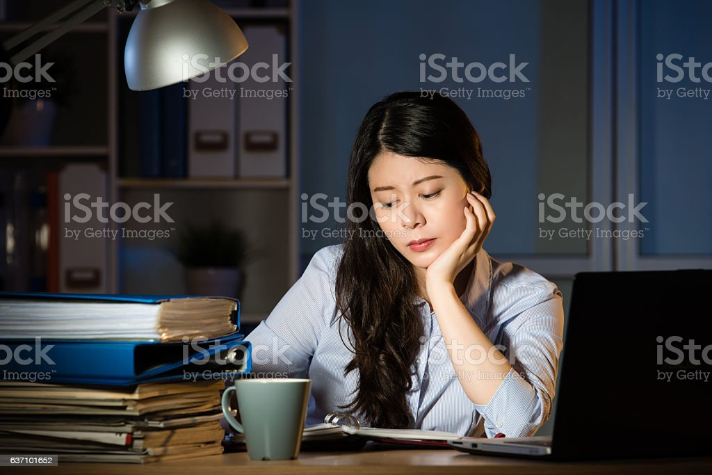 asian business woman working overtime late night in office stock photo