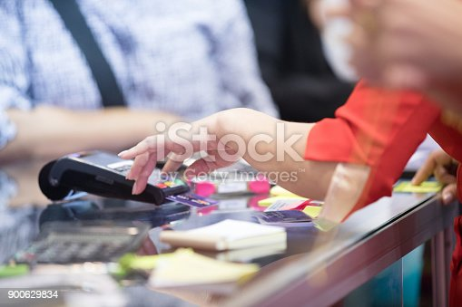 914593772istockphoto Asian Business women hand using credit card swiping machine for payment in cafeteria and supermarket 900629834