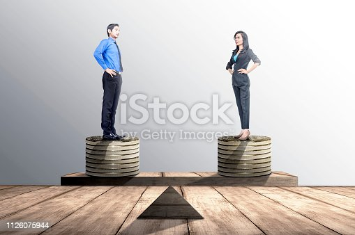 Asian businessman and businesswoman standing on coins stack with same height on balancer. Equality gender concept