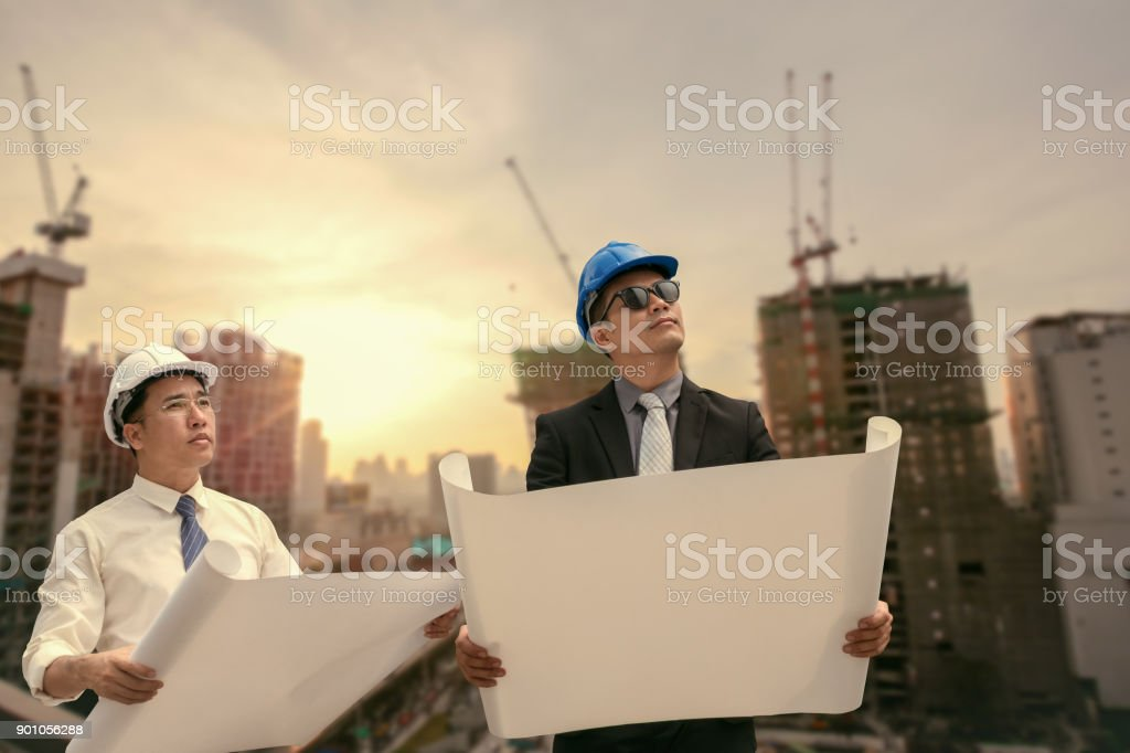 Asian businessman and engineer architect professional occupation corporate city looking away and holding construction idustrial plan for working concept stock photo