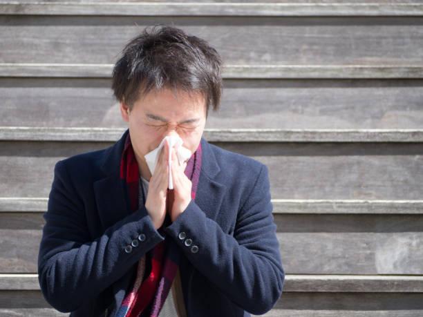 アジア系のビジネスマンが彼の鼻を吹く屋外 - くしゃみ 日本人 ストックフォトと画像