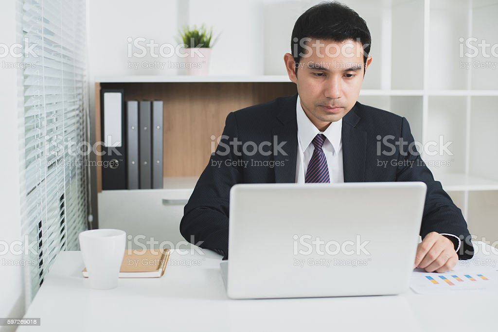 Asian businessman concentrating on using laptop computer Lizenzfreies stock-foto