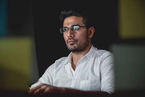 Asian businessman concentrating on working at night Handsome Asian businessman concentrating on working at night with serious face male likeness stock pictures, royalty-free photos & images