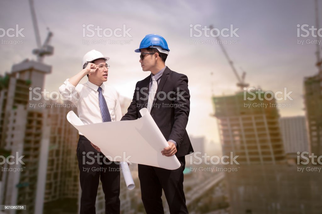 Asian businessman discuss with engineer architect professional occupation corporate city looking away and holding construction idustrial plan for working concept stock photo