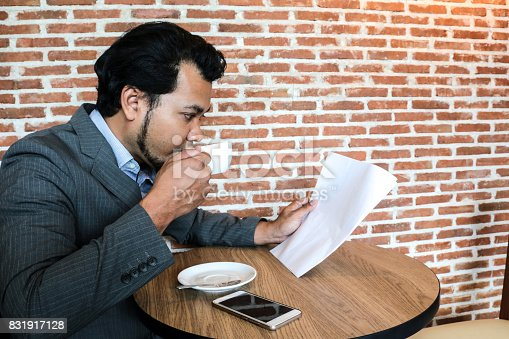 istock Asian businessman drinking hot coffee in white cup while reading the document in coffee shop with background is brick wall. 831917128