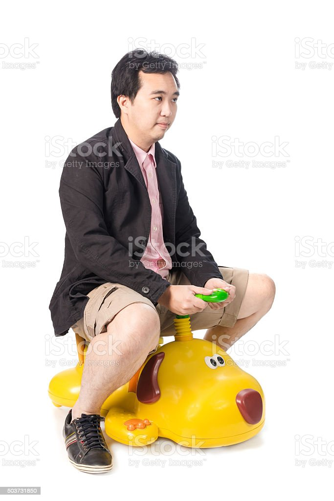 Asian businessman driving a baby toy car look like dog stock photo