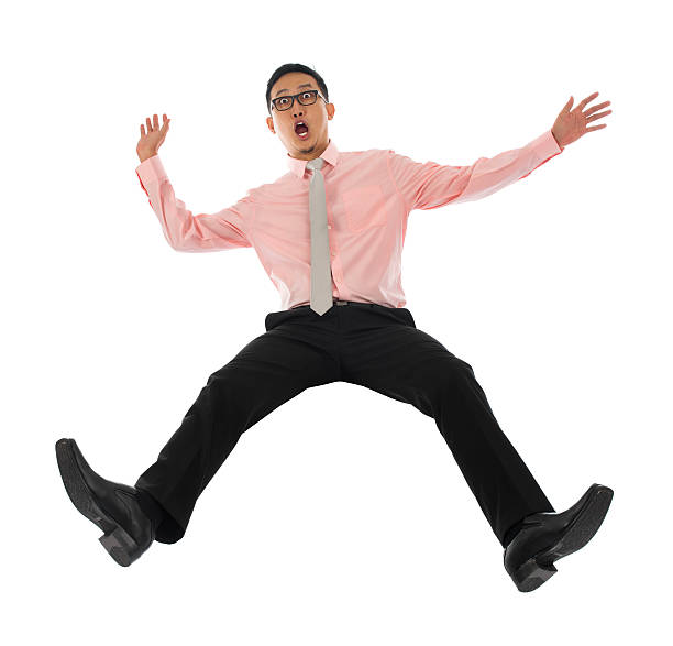 Asian businessman falling backwards Full body shocked young Asian businessman falling backwards open arms, isolated on white background bending over backwards stock pictures, royalty-free photos & images