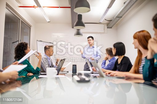 1150572092istockphoto Asian businessman giving presentation to colleagues 1150572134