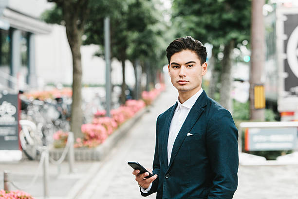asian businessman holding a phone on the street - japanische haarschnitt stock-fotos und bilder