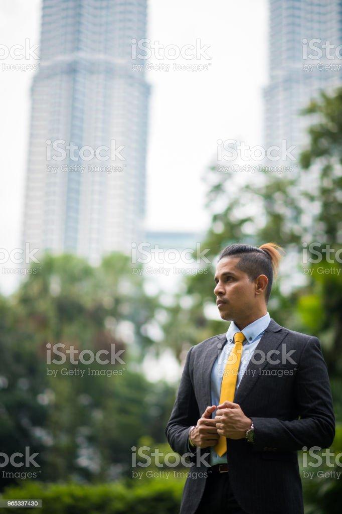 Asian businessman in front of the Petronas Towers zbiór zdjęć royalty-free