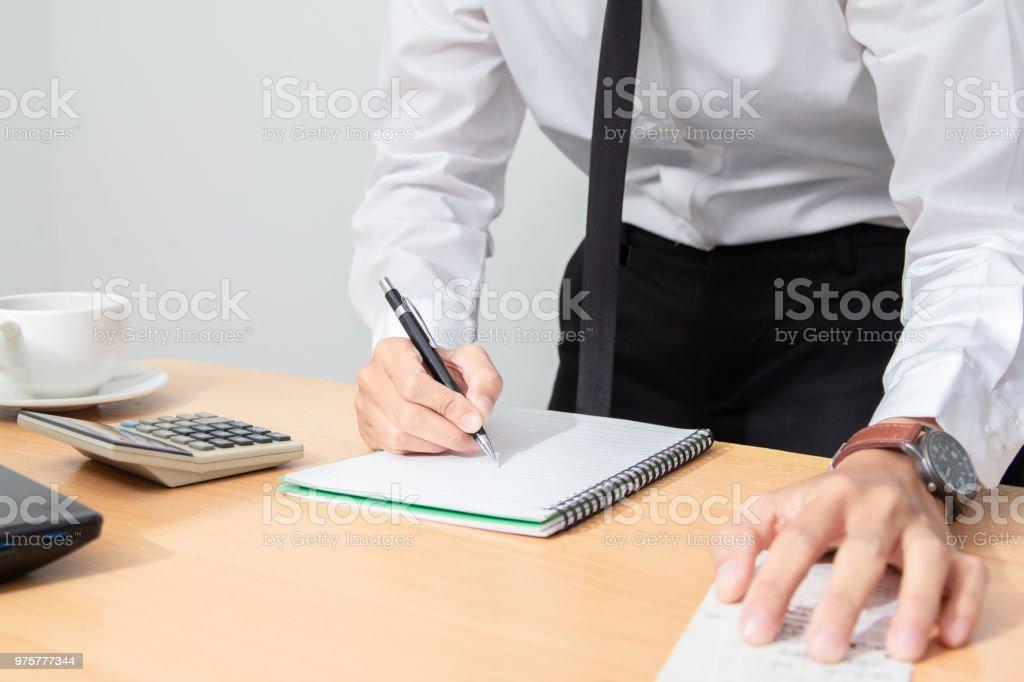 Asiatische Geschäftsmann in weißes Hemd und schwarze Krawatte, die Steuer führt zu der Siedlung Liquidation zu berechnen. - Lizenzfrei Auflösung Stock-Foto