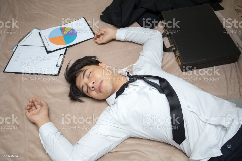 Asian businessman is deep sleeping in his bed at night. businessman tired concept. stock photo