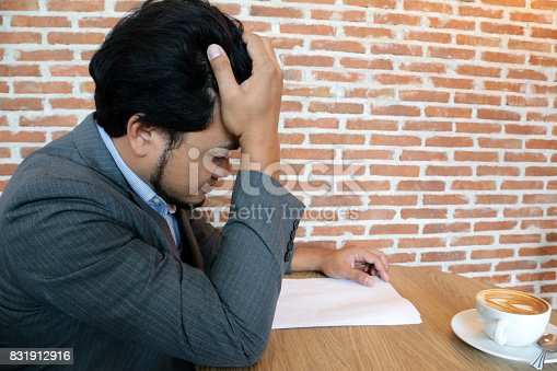 istock Asian Businessman is stressful to read a document during a coffee break. 831912916