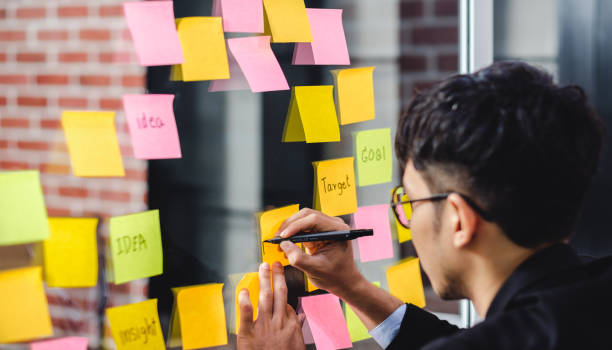 asian businessman looking and writing on sticky note for brainstorming ideas on clear whiteboard at modern office. analyse and synthesis stock photo