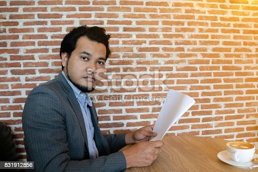 istock Asian businessman looking at the person make sound noise while he reading the document in coffee shop with orange light at brick wall 831912856