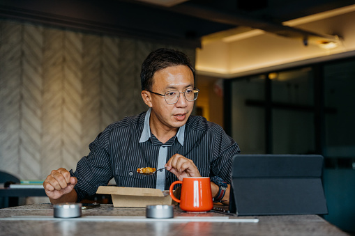 Image of an Asian Chinese businessman making a video call with digital tablet while having his lunch.