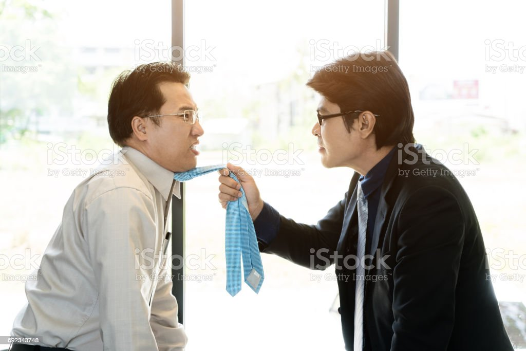 Asian businessman manager shouting to a stressed employee in office on meeting. Fighting businessmen tearing each other at their ties. stock photo