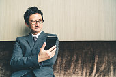 Asian businessman or entrepreneur smiling at smartphone in office or conference room. Business communication or technology gadget concept, with copy space