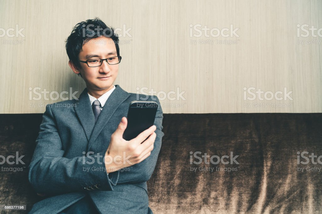 Asian businessman or entrepreneur smiling at smartphone in office or conference room. Business communication or technology gadget concept, with copy space stock photo