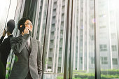Asian businessman or entrepreneur using mobile phone, business or communication technology concept, lens flare effect, with copy space