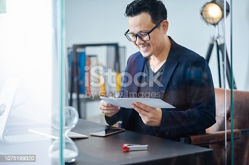 Asian businessman receive a letter with good news in a office .